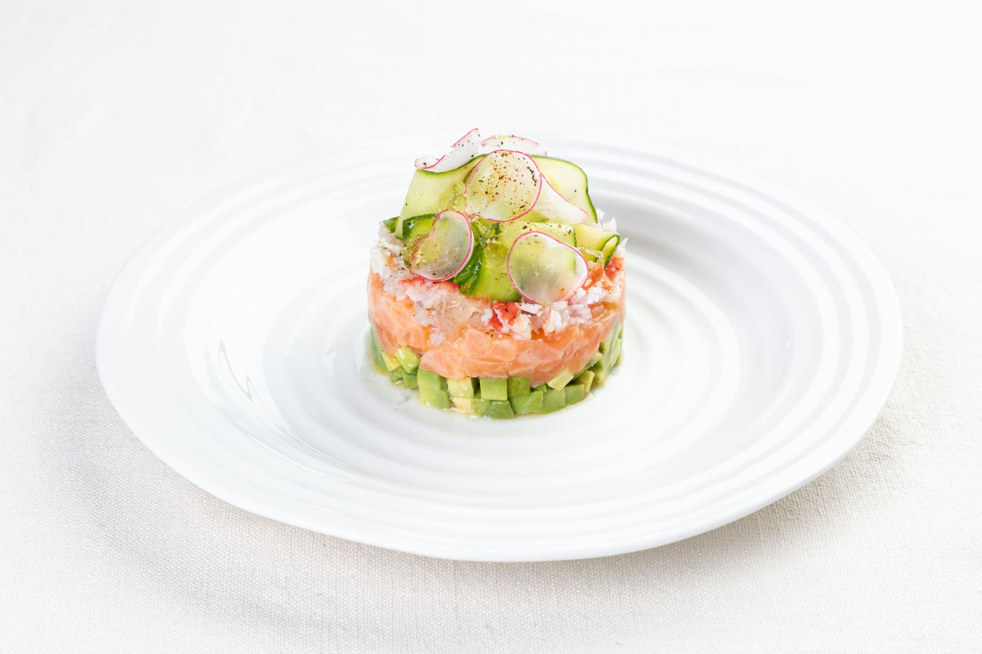 Salmon tartare with avocado, crab and cucumber slices